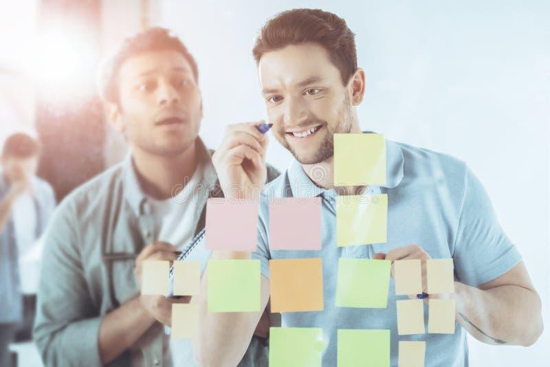 glimlachende jonge zakenman die op kleverige nota's schrijven terwijl geschokte collega status royalty-vrije stock fotografie
