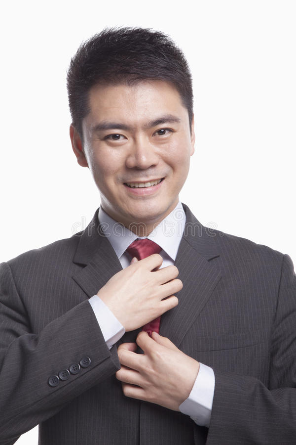 Glimlachende jonge zakenman die zijn band, studioschot aanpassen stock afbeelding