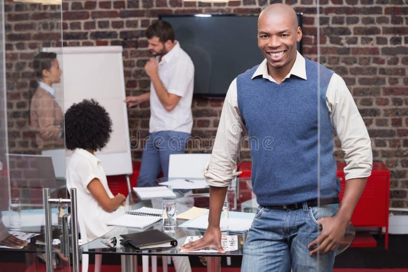 Glimlachende jonge zakenman met collega's op achtergrond royalty-vrije stock fotografie