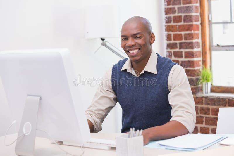 Glimlachende jonge zakenman met computer bij bureau stock fotografie