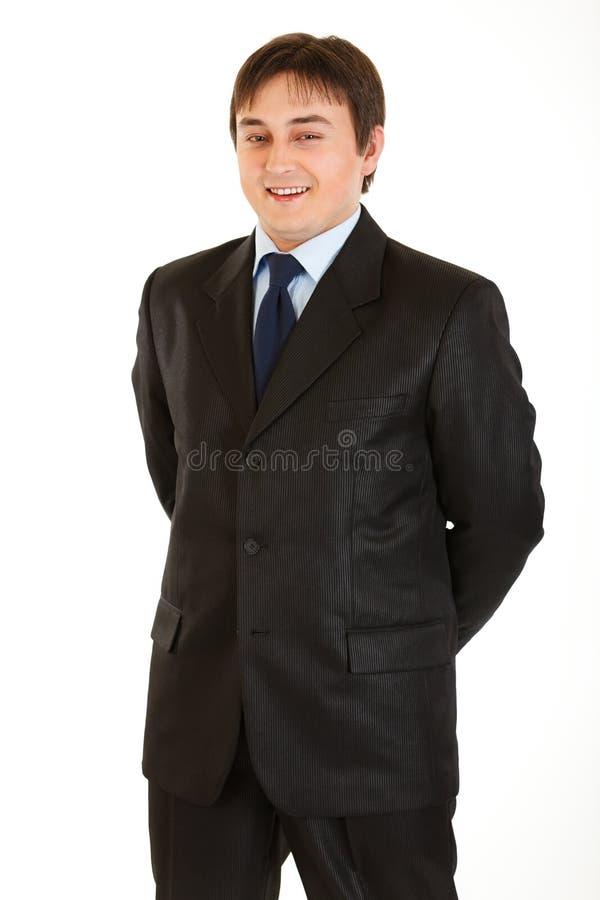Glimlachende jonge zakenman met handen achter rug royalty-vrije stock foto's