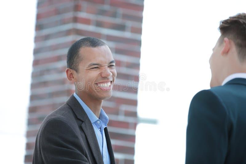 Glimlachende jonge zakenman op achtergrond van bureau royalty-vrije stock afbeelding