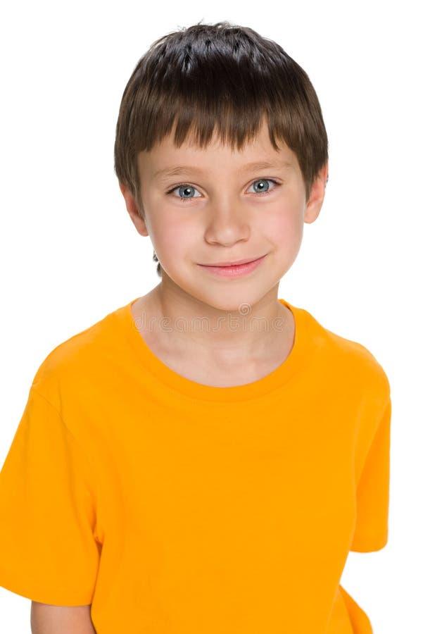 Glimlachende jongen in de gele overhemdstribunes royalty-vrije stock afbeeldingen