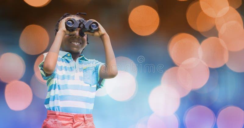 Glimlachende jongen die door verrekijkers over bokeh kijken royalty-vrije stock foto