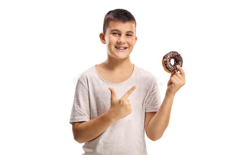 Glimlachende jongen die een chocolade doughnut en het richten houden stock afbeelding