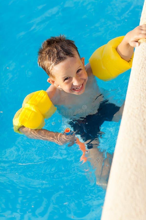 Glimlachende jongen die een pret hebben bij zwembad royalty-vrije stock afbeeldingen