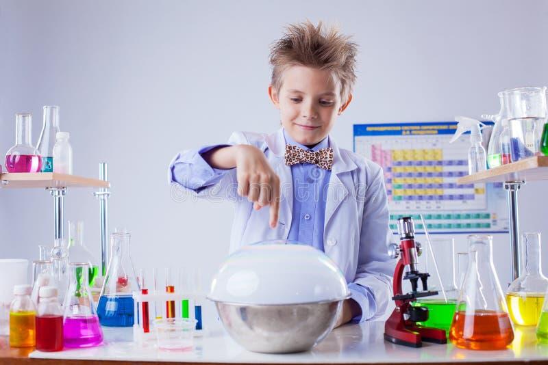 Glimlachende jongen die experiment in chemielaboratorium leiden stock fotografie