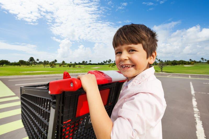 Glimlachende jongen die het boodschappenwagentje duwen bij zebrapad stock afbeelding
