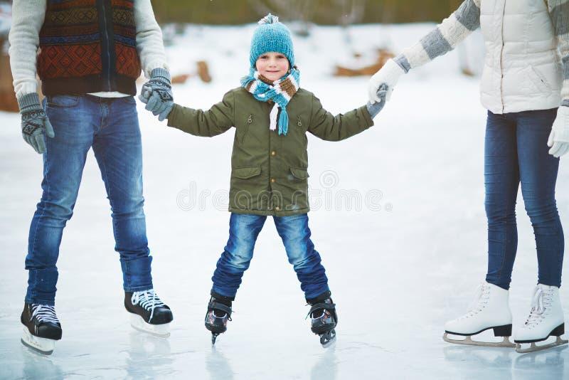 Glimlachende jongen die met ouders schaatsen royalty-vrije stock fotografie