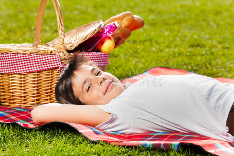 Glimlachende jongen die op gras naast picknickmand leggen stock fotografie