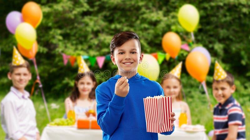 Glimlachende jongen die popcorn eten bij verjaardagspartij royalty-vrije stock fotografie