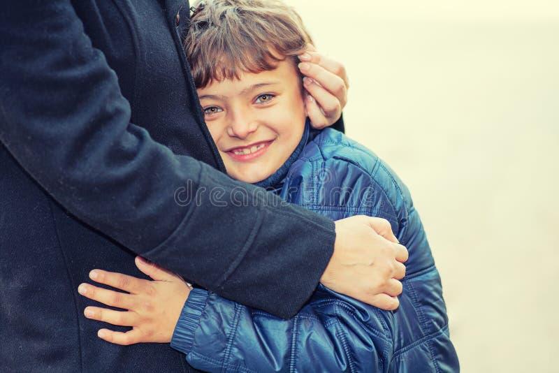 Glimlachende jongen die reusachtig met zijn mammaoudoors hebben stock foto's