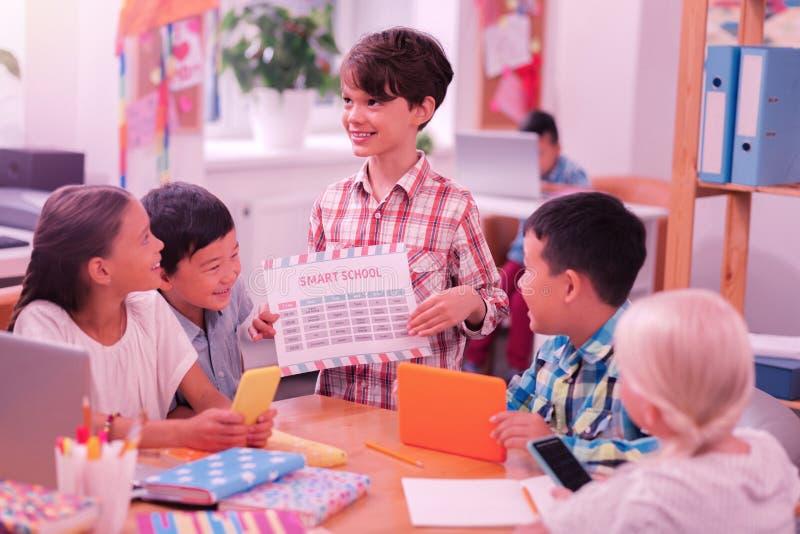 Glimlachende jongen die zich met tijdschema voor zijn vrienden bevinden royalty-vrije stock foto's