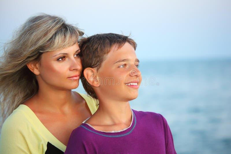 Glimlachende jongen en jonge vrouw op strand in avond stock afbeelding