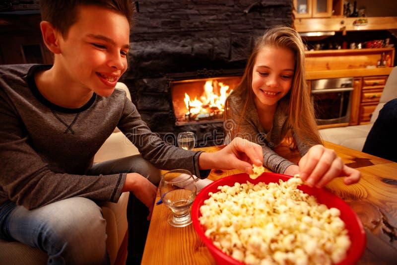 Glimlachende jongen en zijn zuster die popcorn en het hebben van pret eten stock afbeeldingen