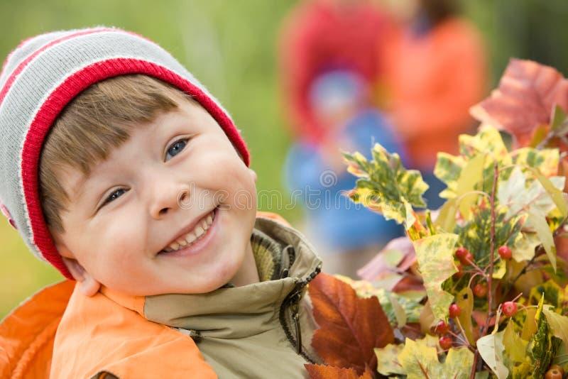 Glimlachende jongen met de herfstbladeren stock foto's