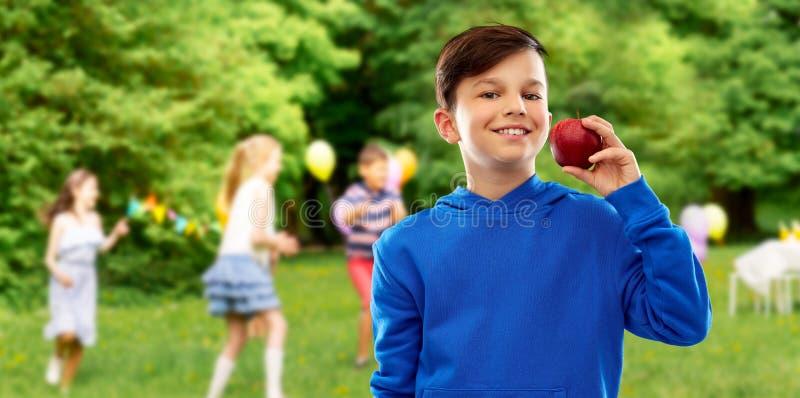Glimlachende jongen met rode appel bij verjaardagspartij stock fotografie