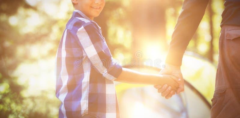 Glimlachende jongen met vader het kamperen in bos stock foto's