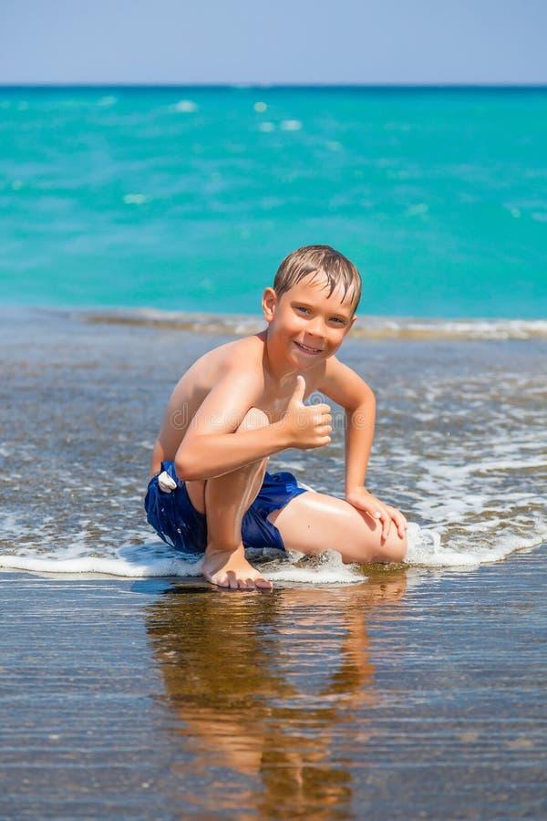 Glimlachende jongen op strand met omhoog duimen stock afbeelding