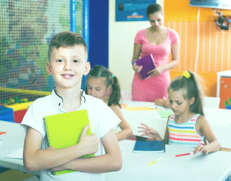 Glimlachende jongensleerling die zich in basisschoolklasse bevinden stock foto