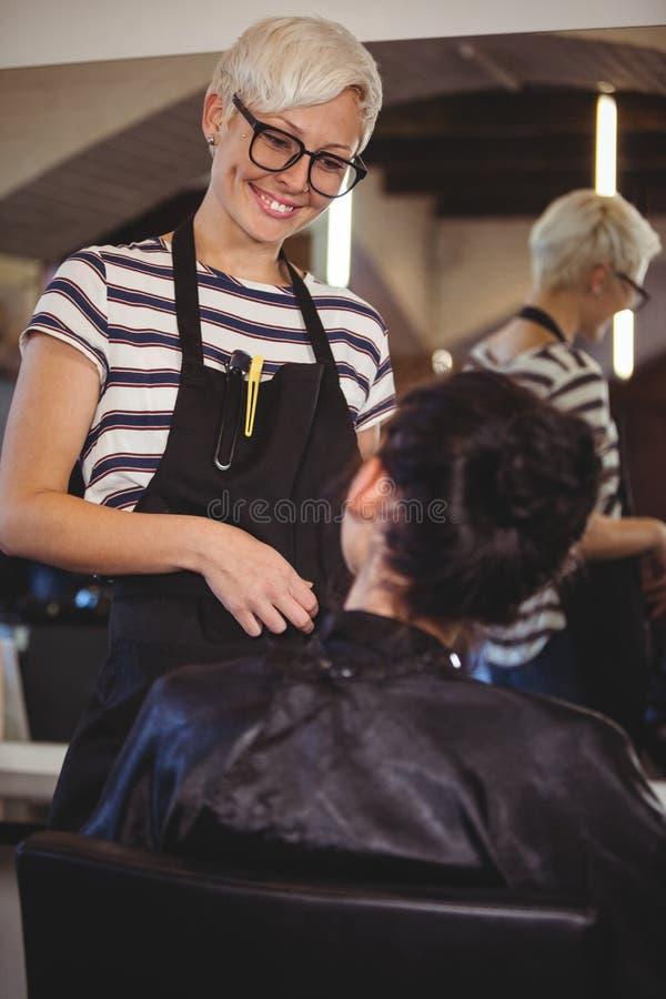 Glimlachende kapper die met cliënt interactie aangaan stock foto's