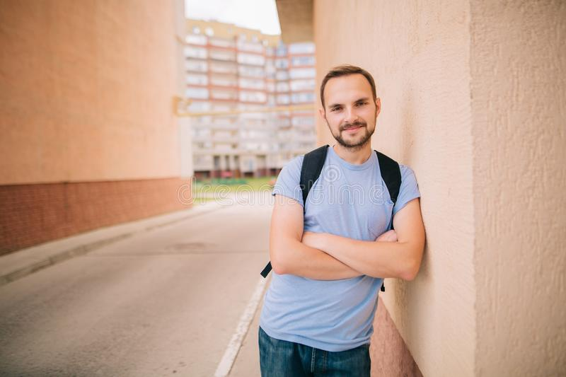 Glimlachende Kaukasische gebaarde studenten jonge mens hipster in blauwe t-shirt met rugzak die zich in boog bevinden die op muur royalty-vrije stock foto
