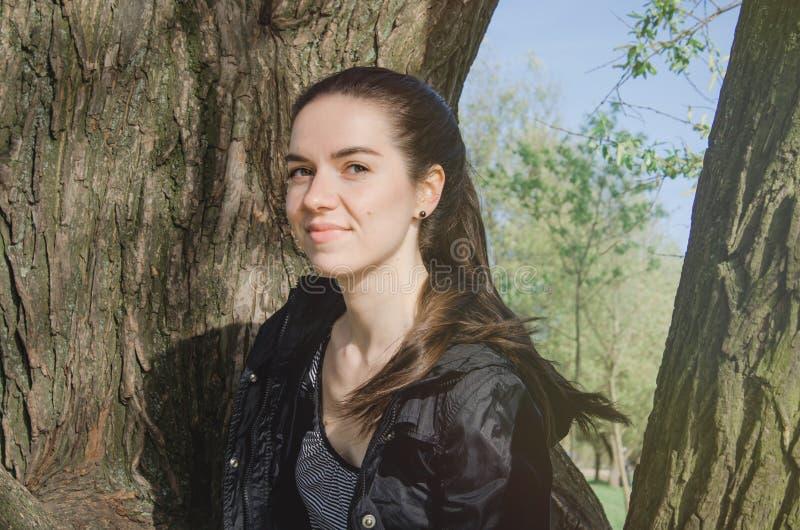 Glimlachende Kaukasische jonge vrouw in zwart jasje, op een achtergrond van de boomaard Openluchtportret van mooi brunette stock fotografie