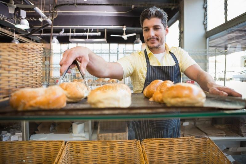 Glimlachende kelner die brood met tang nemen stock foto's