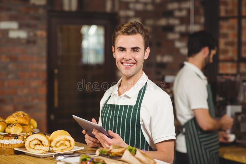 Glimlachende kelner die een digitale tablet houden stock foto