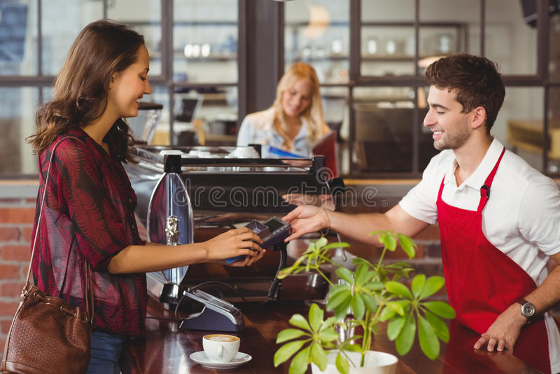 Glimlachende kelner die een speldterminal overhandigen stock foto's