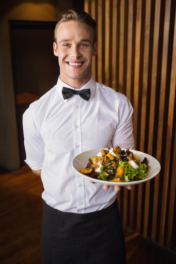 Glimlachende kelner die plaat van salade tonen aan camera stock foto