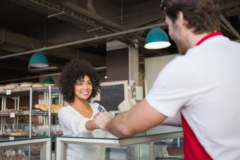 Glimlachende kelner die transactie met klant doen stock afbeeldingen