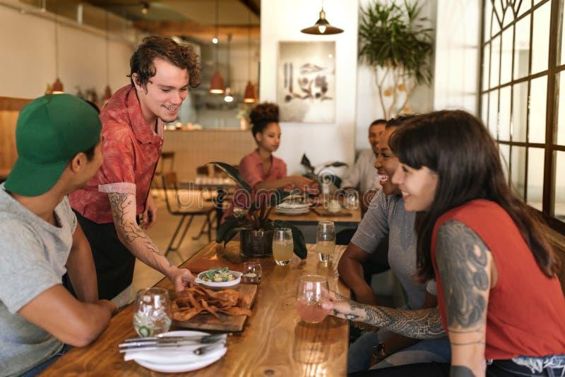 Glimlachende kelner die vers gemaakte tapas dienen aan glimlachende restaurantklanten stock foto's