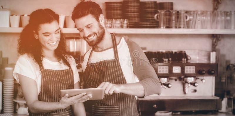 Glimlachende kelner en serveerster die digitale tablet gebruiken bij teller royalty-vrije stock fotografie