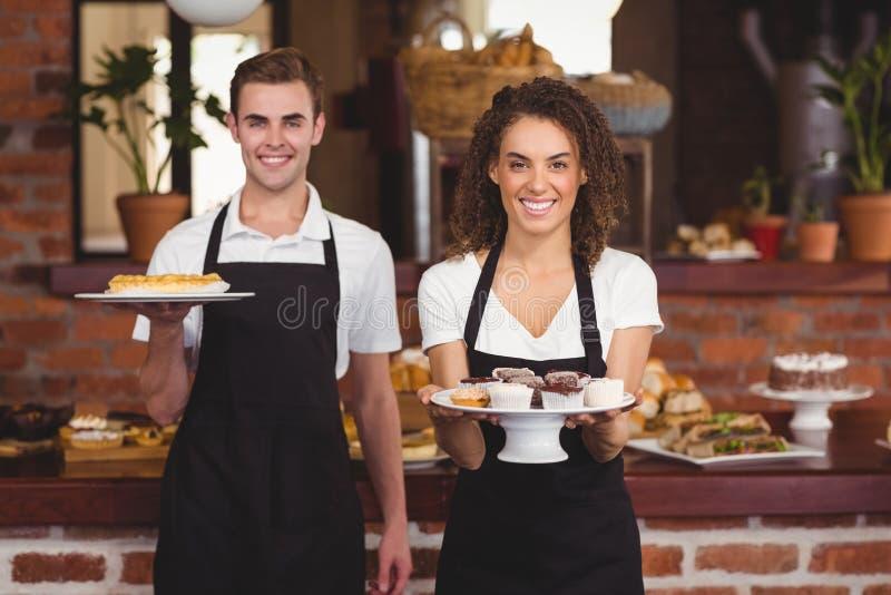 Glimlachende kelner en serveerster die platen met traktatie tonen royalty-vrije stock afbeeldingen
