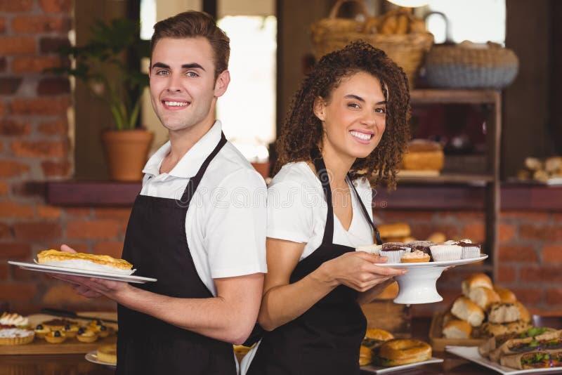 Glimlachende kelner en serveersterholdingsplaten met traktatie stock fotografie