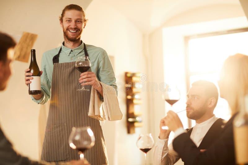 Glimlachende Kelner Serving Wine stock foto