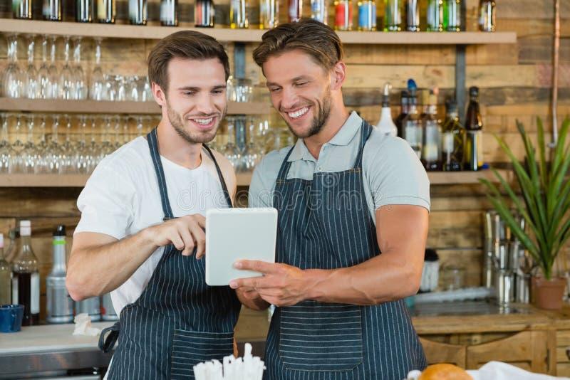 Glimlachende kelners die digitale tablet gebruiken bij teller stock afbeeldingen