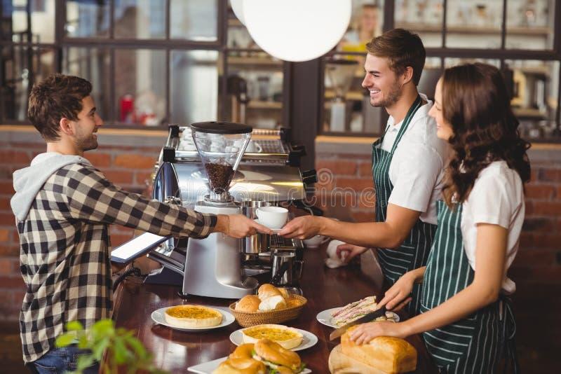 Glimlachende kelners die een cliënt dienen stock afbeelding