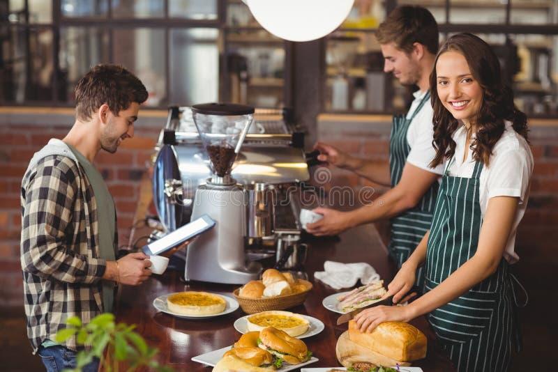 Glimlachende kelners die een cliënt dienen royalty-vrije stock fotografie