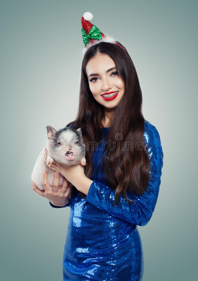 Glimlachende Kerstmisvrouw in blauwe kleding met weinig varken Glimlach en tanden met steunen royalty-vrije stock fotografie