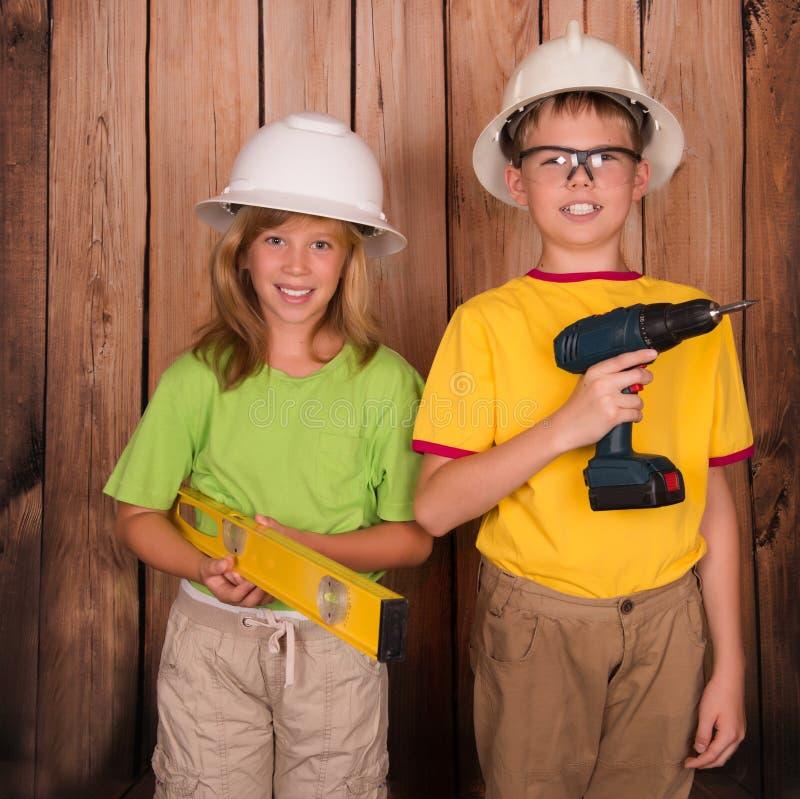 Glimlachende kinderen in bouwvakkers met bouwhulpmiddelen op houten royalty-vrije stock foto