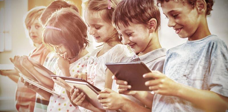 Glimlachende kinderen die digitale tabletten gebruiken stock afbeeldingen