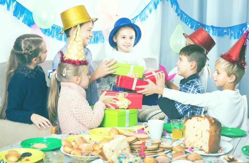 Glimlachende kinderen die giften voorstellen aan meisjesverjaardag royalty-vrije stock afbeelding