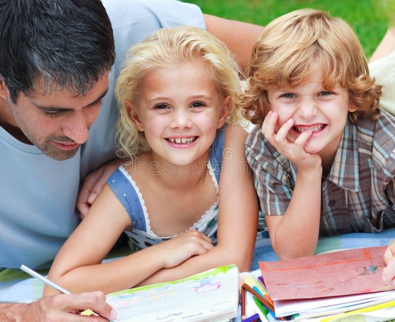 Glimlachende kinderen die met hun vader trekken stock afbeeldingen