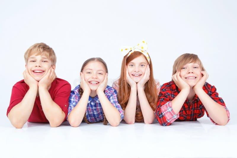 Glimlachende kinderen die op de vloer in ruw liggen royalty-vrije stock afbeelding