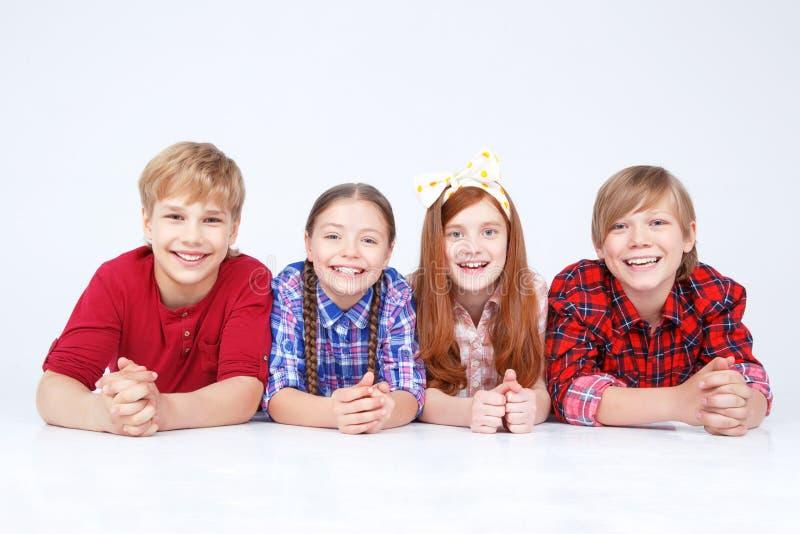 Glimlachende kinderen die op de vloer in ruw liggen stock fotografie