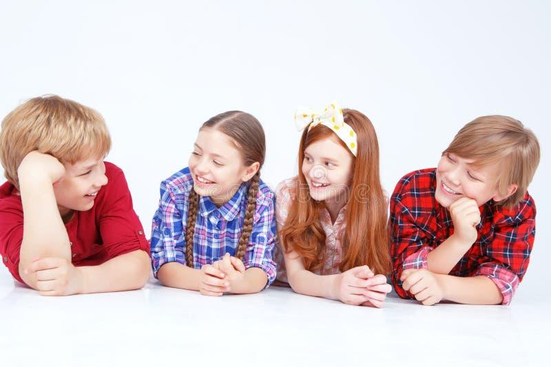 Glimlachende kinderen die op de vloer in ruw liggen stock foto