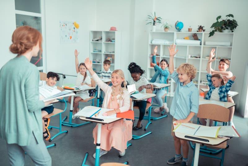Glimlachende kinderen in een klaslokaal die met de leraar in wisselwerking staan stock foto