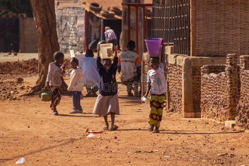 Glimlachende kinderen met emmers water op hun hoofden stock foto's